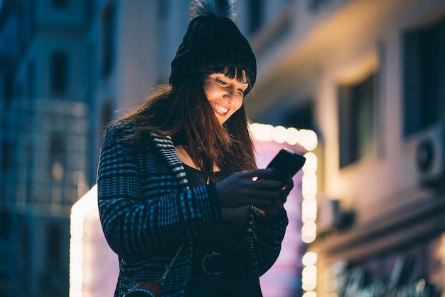Retrato de mujer morena mirando smartphone por la noche