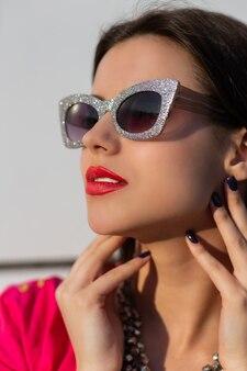Retrato de mujer morena de moda en elegantes gafas de sol y camiseta rosa de cerca.