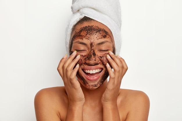 Retrato de mujer morena sonriente alegre aplica mascarilla de café natural, hace movimientos circulares con las manos y masajea la piel, estimula el riego sanguíneo facial, usa una toalla envuelta en la cabeza.