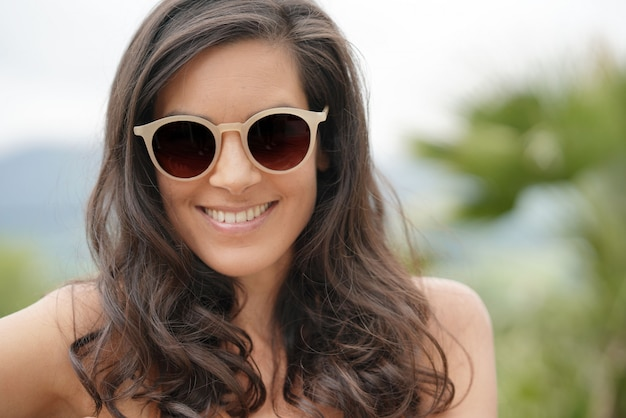 Retrato de la mujer morena sonriente que lleva las gafas de sol