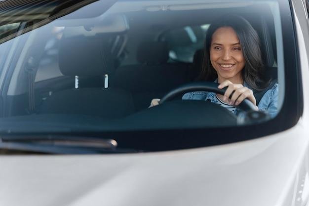 Retrato de mujer morena en su coche