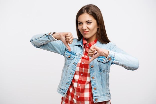 Retrato de mujer mostrando pulgares abajo gesto en pared blanca