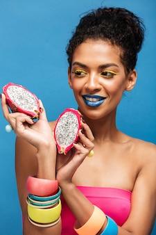 Retrato de mujer mulata sonriente con cosméticos brillantes en la cara degustación de pitahaya madura cortada por la mitad aislada, sobre pared azul
