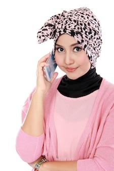 Retrato de una mujer musulmana asiática hablando por teléfono celular
