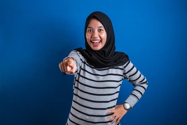 Retrato de mujer musulmana asiática con hijab apuntando hacia la cámara como si eligiera su gesto, concepto de contratación de contratación empresarial