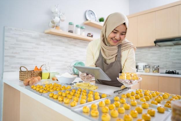 Retrato de mujer musulmana feliz con bocadillo nastar en la cocina