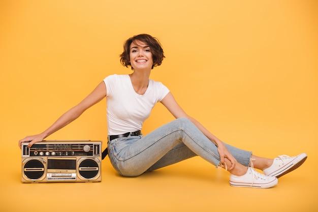 Retrato de una mujer muy alegre sentada con tocadiscos