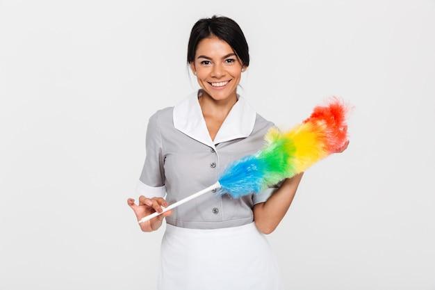 Retrato de mujer muy sonriente en uniforme con colorido limpiador de polvo