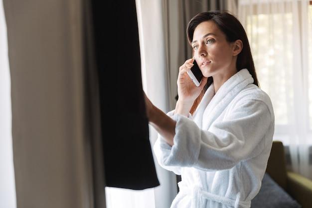 Retrato de mujer de negocios adulta atractiva en bata de baño blanca hablando por teléfono celular mientras mira su traje formal en el apartamento