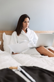 Retrato de mujer de negocios adulta caucásica en bata de baño blanca trabajando con documentos en papel y portátil mientras está acostado en la cama en el apartamento