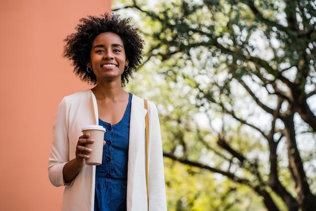 Retrato de mujer de negocios afro sonriendo y sosteniendo una taza de café mientras está de pie al aire libre en la calle. concepto urbano y empresarial.