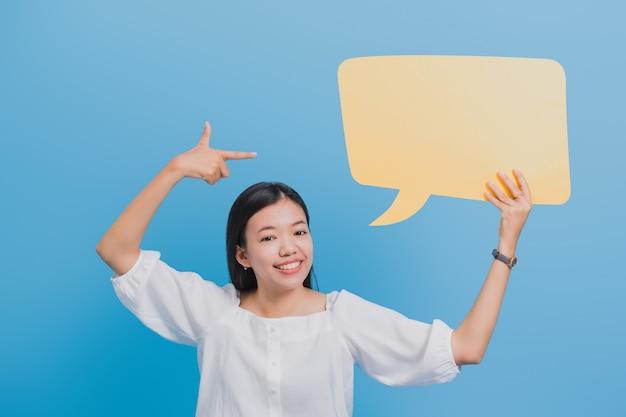 Retrato de la mujer de negocios asiática hermosa confiada que coloca y que lleva a cabo discurso amarillo en blanco de la burbuja.