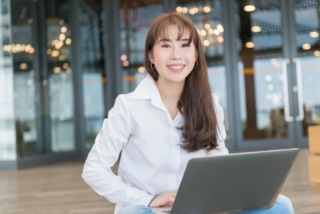 Retrato de la mujer de negocios asiática joven en la camisa blanca usando la computadora portátil al aire libre.