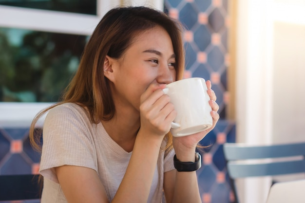 Retrato de la mujer de negocios asiática joven feliz con la taza en manos que bebe el café por la mañana