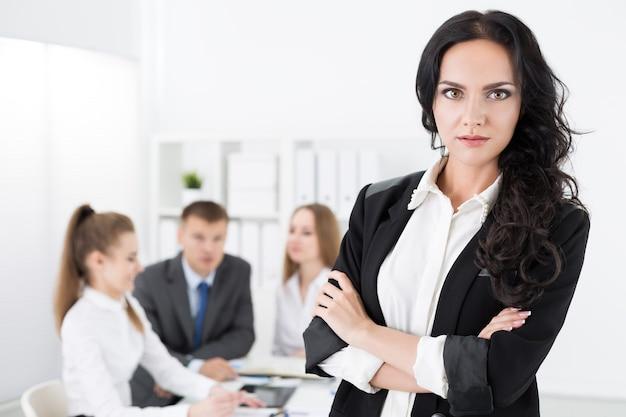 Retrato de mujer de negocios bastante joven de pie con los brazos cruzados sobre el pecho frente a su equipo