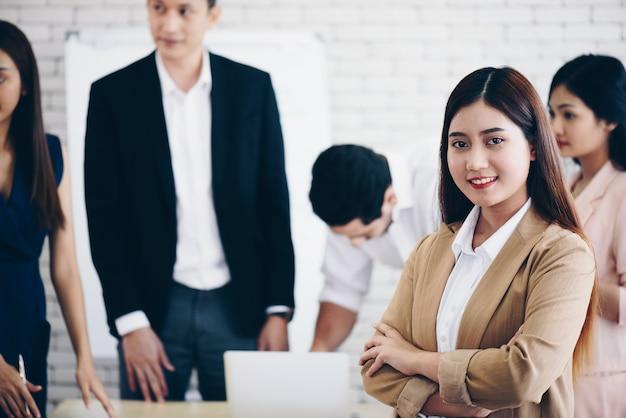 Retrato de mujer de negocios bastante joven sonriente con trabajo en equipo de desenfoque