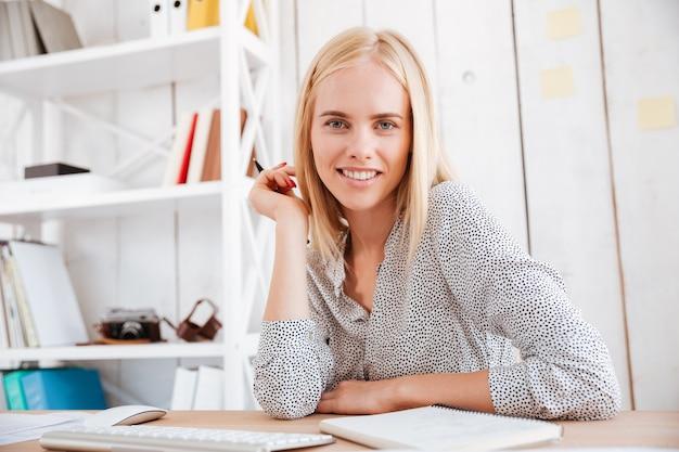 Retrato de una mujer de negocios bonita sonriente mirando al frente mientras está sentado en el lugar de trabajo