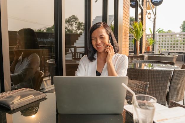 Retrato de mujer de negocios en un café usando una computadora portátil y hablando con teléfono celular