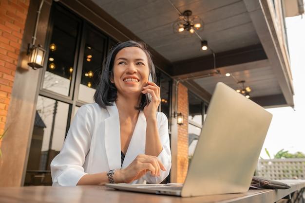 Retrato de mujer de negocios en un café usando una computadora portátil y hablando por un teléfono móvil