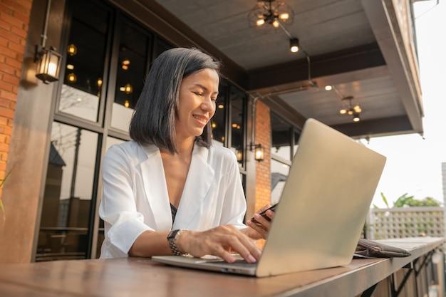 Retrato de mujer de negocios en un café usando una computadora portátil y un teléfono móvil