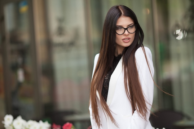 Retrato de mujer de negocios caminando y sonriendo al aire libre