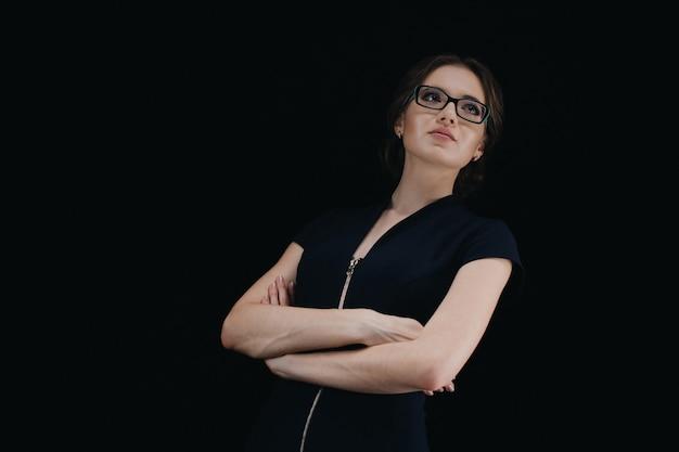 Retrato de la mujer de negocios caucásica joven atractiva con los brazos cruzados en negro