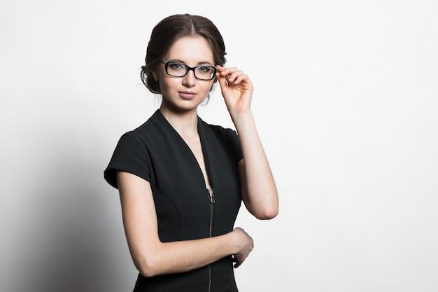 Retrato de la mujer de negocios caucásica joven atractiva que sostiene los vidrios con su mano en gris