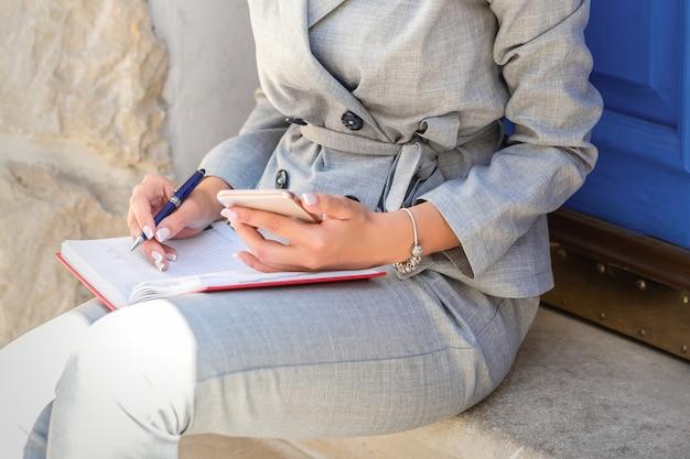 Retrato de mujer de negocios caucásica joven hermosa que se sienta con el teléfono celular y el bloc de notas en la puerta