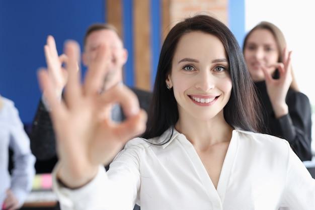 Retrato de mujer de negocios demuestra gesto ok contra el fondo de los colegas de negocios