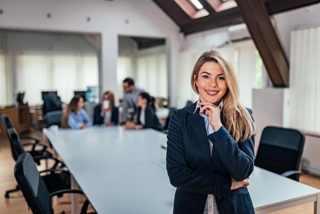 Retrato de una mujer de negocios con un equipo en la reunión