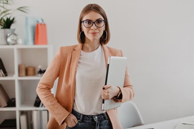 Retrato de mujer de negocios exitosa con gafas y chaqueta ligera sonriendo contra la oficina blanca.