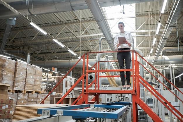Retrato de mujer de negocios en la fábrica de carpintería con tablet pc