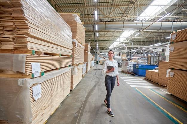 Retrato de mujer de negocios en la fábrica de carpintería con tableta