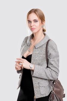 Retrato de mujer de negocios hermosa joven rubia en vestido negro, chaqueta y con bolsa sobre fondo gris