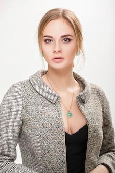Retrato de mujer de negocios hermosa joven rubia en vestido negro, chaqueta sobre fondo gris