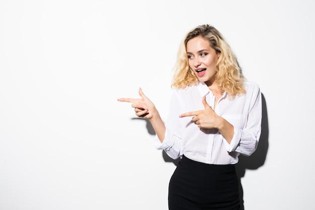 Retrato de mujer de negocios joven apuntando hacia el lado en la pared blanca