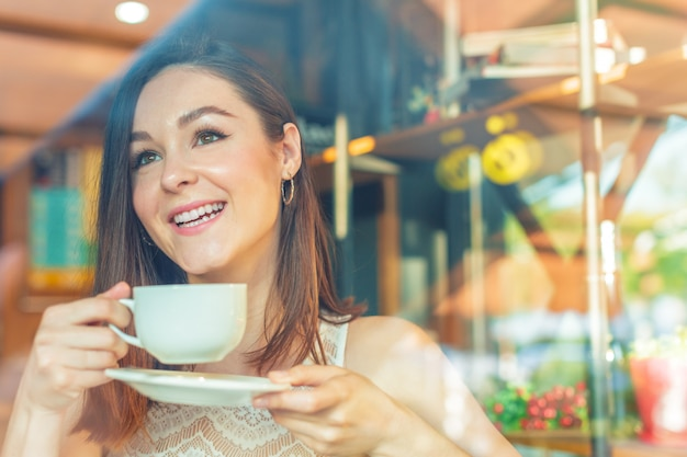 Retrato de mujer de negocios joven feliz con taza en las manos tomando café en el restaurante
