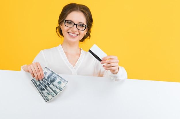 Retrato de mujer de negocios joven hermosa confiada con dinero y tarjeta de crédito en sus manos
