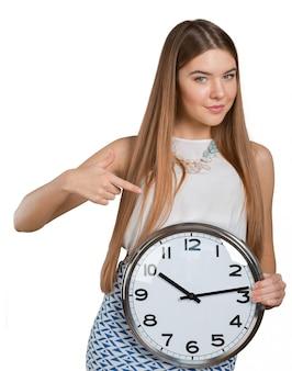 Retrato de la mujer de negocios joven hermosa que se sostiene en reloj de las manos