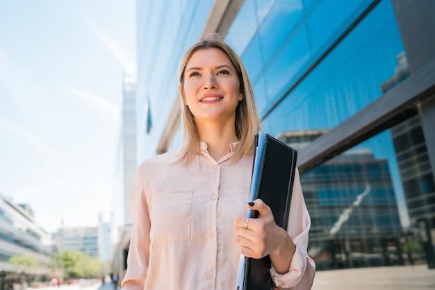 Retrato de mujer de negocios joven de pie fuera de los edificios de oficinas. concepto de negocio y éxito.