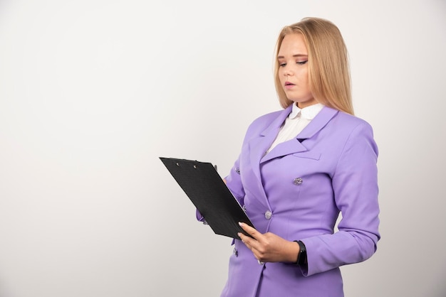 Retrato de mujer de negocios joven de pie y mirando en el portapapeles. foto de alta calidad