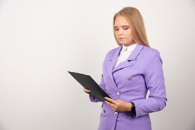 Retrato de mujer de negocios joven de pie y mirando en el portapapeles.