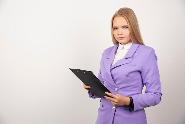 Retrato de mujer de negocios joven de pie y sosteniendo el portapapeles.