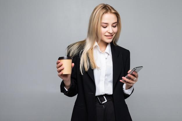 Retrato de una mujer de negocios joven satisfecha que usa el teléfono móvil mientras sostiene la taza de café para ir aislado