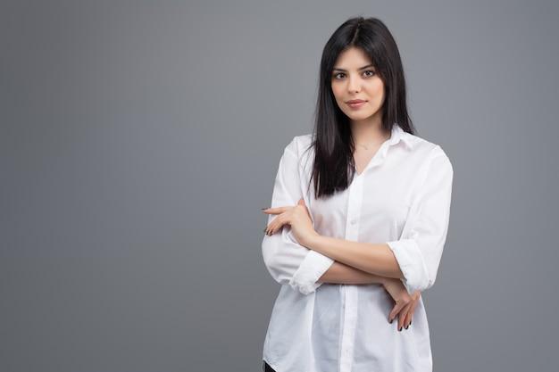 Retrato de una mujer de negocios joven sonriente en camisa blanca