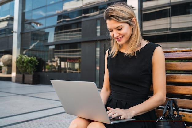 Retrato de mujer de negocios joven usando su computadora portátil mientras está sentado al aire libre en la calle. concepto de negocio.