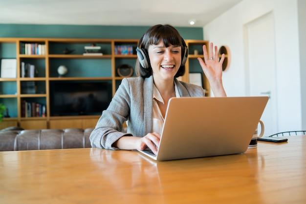 Retrato de mujer de negocios joven en videollamada con portátil y auriculares. concepto de oficina en casa. nuevo estilo de vida normal.