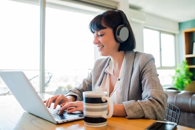 Retrato de mujer de negocios joven en videollamada con portátil y auriculares. concepto de oficina en casa