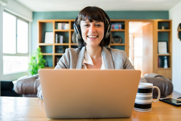 Retrato de mujer de negocios joven en videollamada con portátil y auriculares