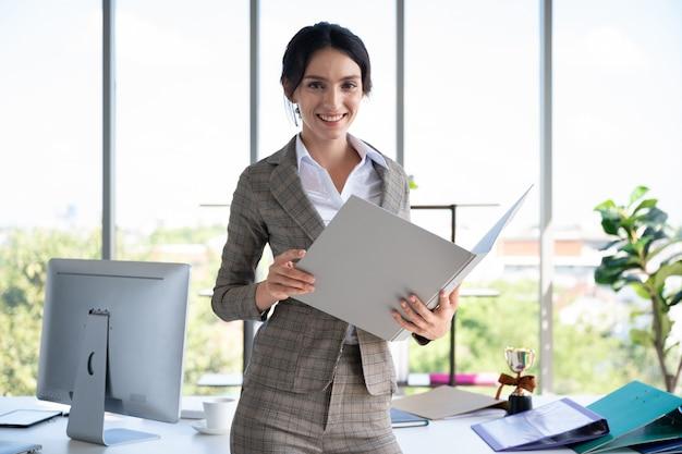 Retrato de mujer de negocios con libro en la oficina moderna